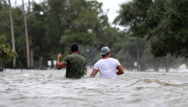 Dos personas caminan por una calle inundada en la localidad de Mandeville.