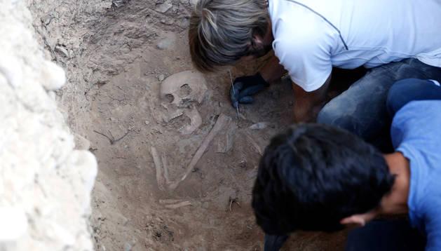 Foto de dos integrantes del taller de arqueología de 2018 trabajando sobre los restos óseos hallados.