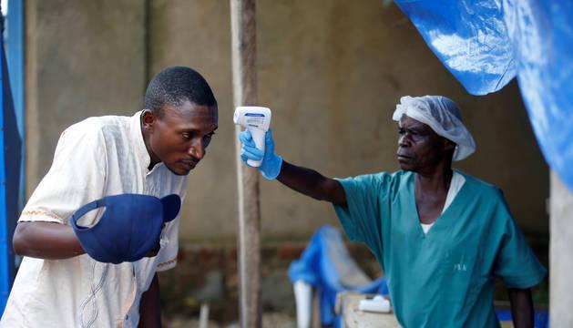 Foto de dos trabajadores sanitarios toman las medidas necesarias ante la epidemia de ébola detectada en el país.