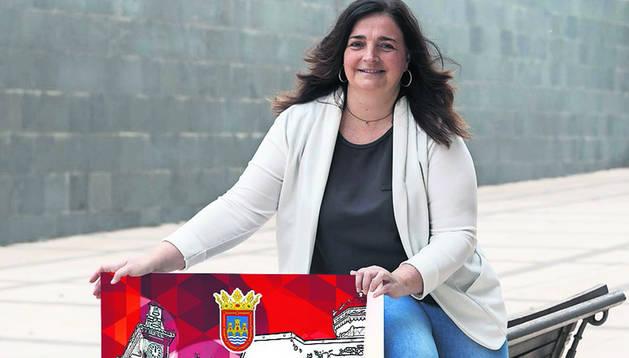 Foto de Laura Casajús junto a su cartel, que anuncia las fiestas de 2019.