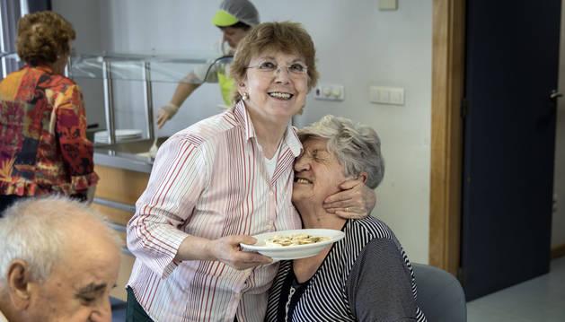Foto de un gesto cariñoso entre dos de las usuarias del comedor del centro de mayores Oskia, en el barrio de San Juan.