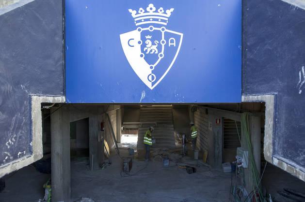 Foto de dos obreros trabajando en la mejora de las escaleras de acceso.