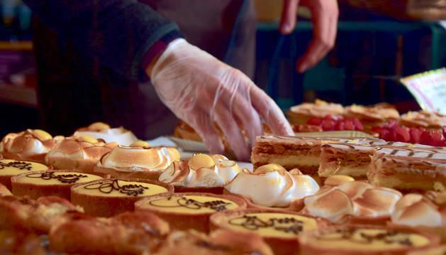 Foto de un repostero preparando diferentes tipos de dulces y pasteles.