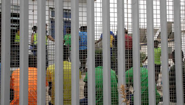 Un grupo de inmigrantes subsaharianos tras el muro del Centro de Estancia Temporal de Inmigrantes (CETI).