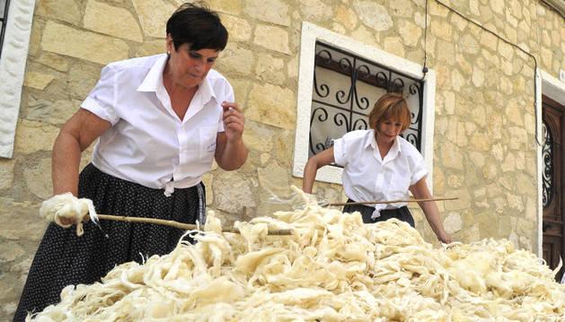 De izquierda a derecha: Mari Carmen Ituria y Angelina Jiménez varean con palo de fresno la lana de los colchones para desapelmazarlos.