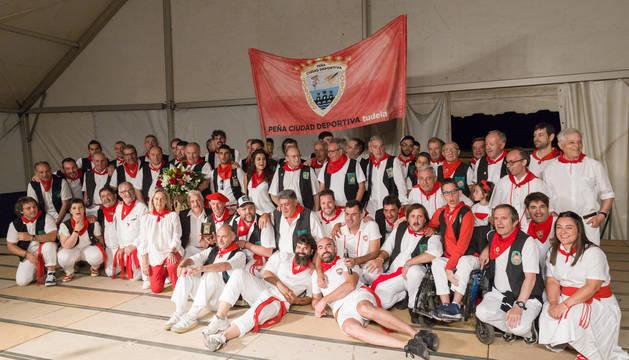 Foto de los integrantes de la peña La Teba, con chalecos negros, junto con Tudelanos Populares de otras ediciones y representantes de la entidad organizadora.