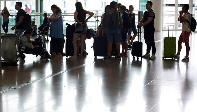 Foto de varias personas esperan en el aeropuerto del Prat, Barcelona.
