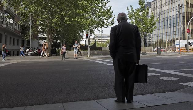 Foto de un hombre que aguarda con su maletín a que se abra el semáforo para cruzar una calle.