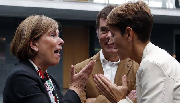 Foto de la socialista María Chivite habla con Uxue Barkos (Geroa Bai) ayer en el atrio del Parlamento, con el secretario general de Podemos, Eduardo Santos, de testigo.