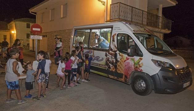 Foto de varios niños guardan cola frente a la furgoneta del heladero ambulante, ya de madrugada en Artavia, valle de Allín.