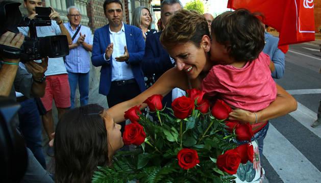 Foto de los dos hijos de María Chivite, que le esperaban cerca de la sede socialista con un ramo de rosas rojas y una bandera del PSOE.
