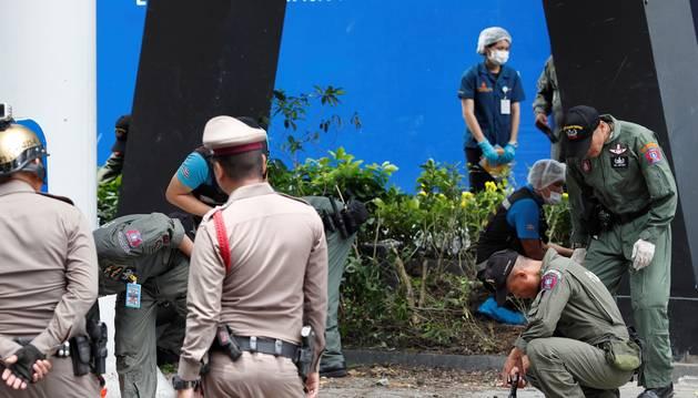 Foto de varios agentes de la policía tailandesa, que inspeccionan el área donde ha explotado una bomba en Bangkok.
