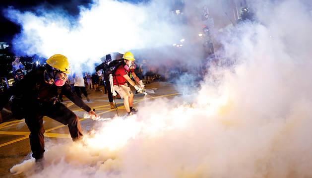Dos manifestantes vacían botes de humo durante las protestas.