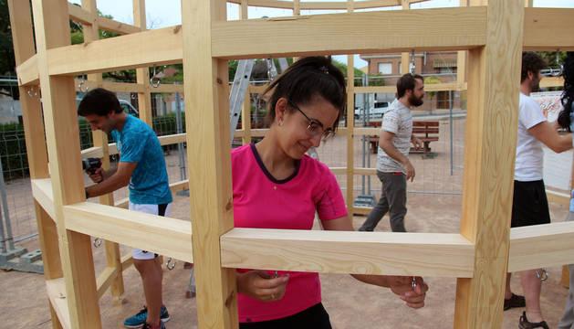 Foto de varios voluntarios, mientras construyen la estructura de madera.