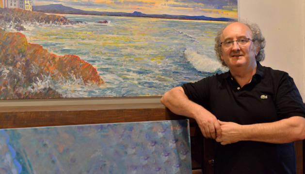 El artista navarro Juan Carlos Pikabea junto al cuadro 'La Costa vasca desde Biarritz' de su exposición en su casa en Lesaka.