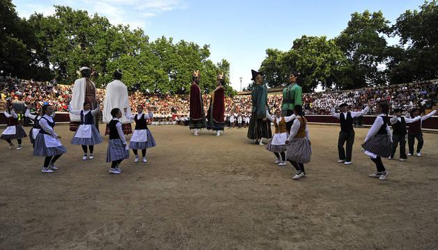 La comparsa de gigantes de Tafalla baila ante una plaza de toros abarrotada de público para celebrar su centenario.