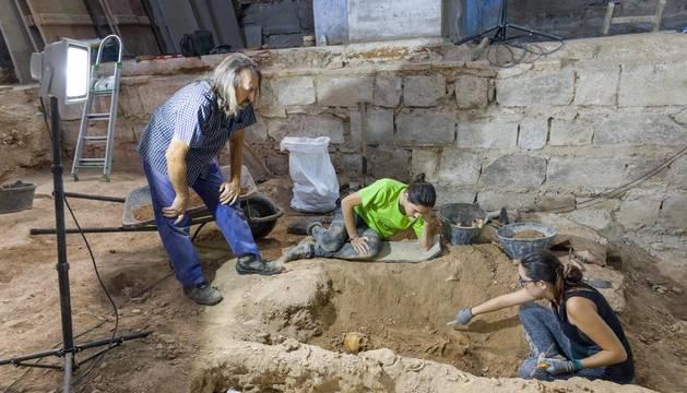 Juanjo Bienes, a la izquierda, observa el trabajo de dos de los participantes en las excavaciones.