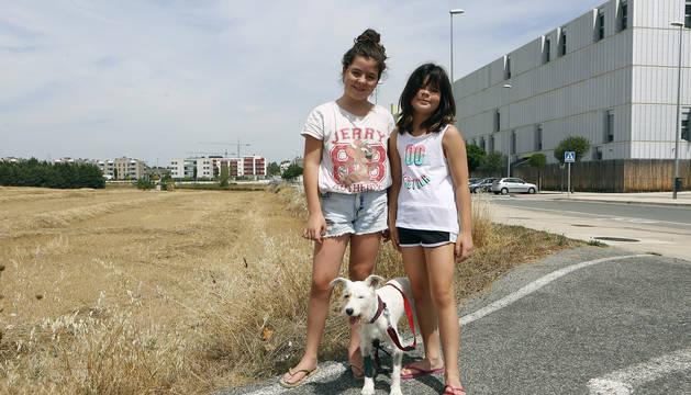 Las hermanas Noa y Kira Rodríguez Belzunce en la carretera donde la víbora le picó a su perra Luna, junto a ellas.