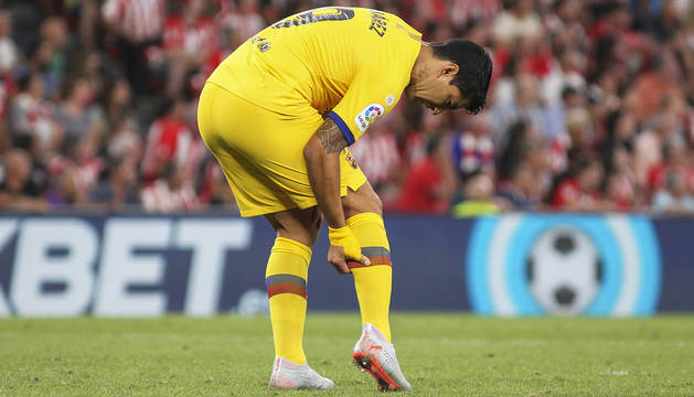 Luis Suárez se echa las manos a la pierna derecha al sentir las molestias durante el encuentro en San Mamés.