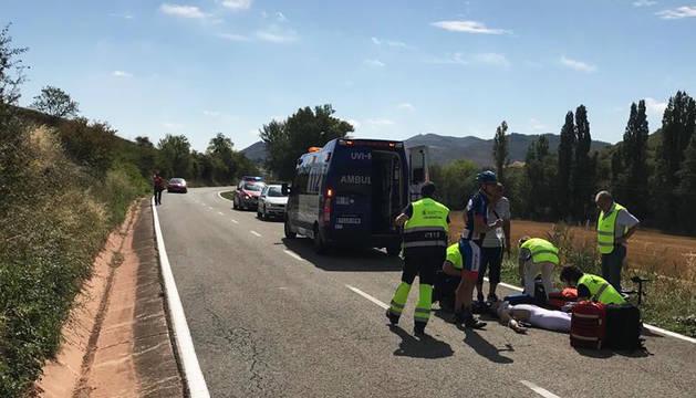 Un ciclista que acompañaba al herido junto al accidentado mientras es atendido por los sanitarios en el lugar del accidente.