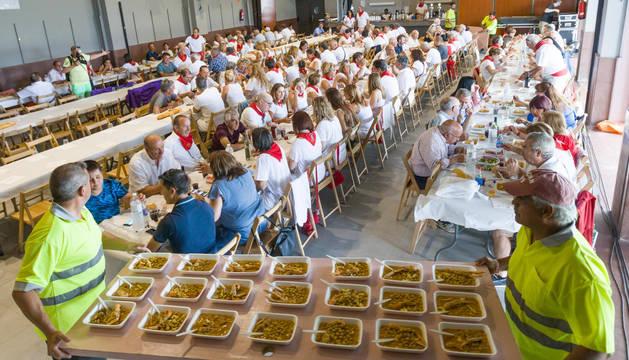 ¡A COMER! Los miembros de la brigada reparten los platos de garbanzos con cigalas y rape en el salón cultural.