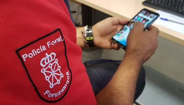 Un agente de Policía Foral con un móvil en la mano.