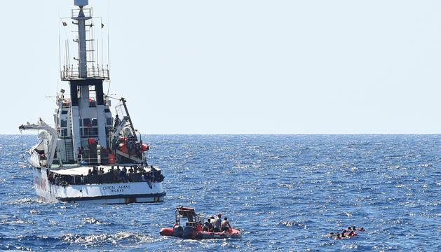 Los migrantes saltan del barco de rescate español Open Arms, cerca de la costa italiana en Lampedusa.
