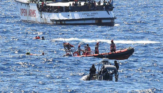 Migrantes nadando en el mar después de saltar del barco de Open Arms.