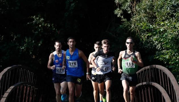 El grupo de cabeza de la carrera, por uno de los puentes que rodea la localidad.