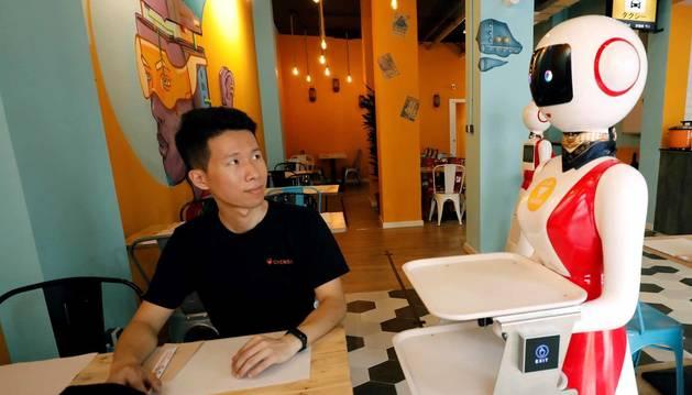 Se llama Crensa y es un restaurante que abre este lunes en el barrio valenciano de Benimaclet, pero con algo que le hace único en España: sus dos camareras son robots, responden al nombre de Mulán y sirven los pedidos con tanta educación como al pedir paso para llevar sus platos y llamar cariño al cliente.En la imagen, el dueño chino del restaurante, Erik Yan