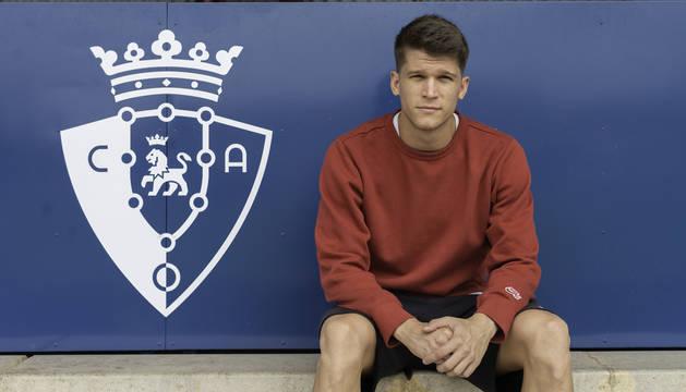Foto de Marc Cardona posando antes de la entrevista con Diario de Navarra sentado en la grada de las instalaciones de Tajonar junto al escudo de Osasuna.