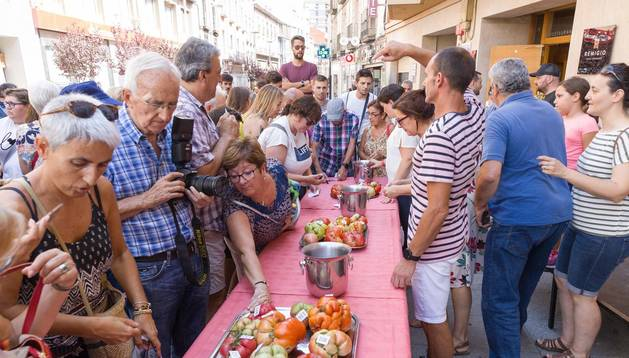 Un grupo de personas contempla los ejemplares que se presentaron a la categoría del tomate más 'feo', que fue elegido por votación popular.