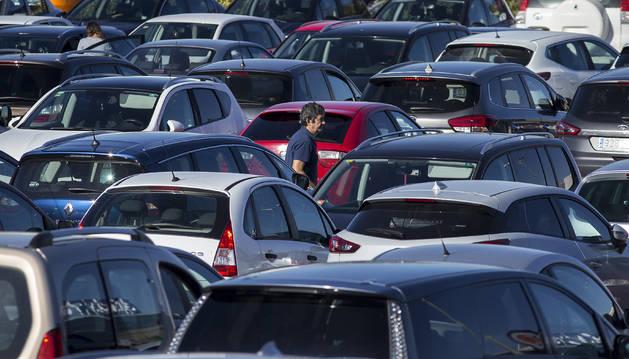 Foto de un hombre camina entre coches en el aparcamiento del hipermercado E.Leclerc de Cordovilla.