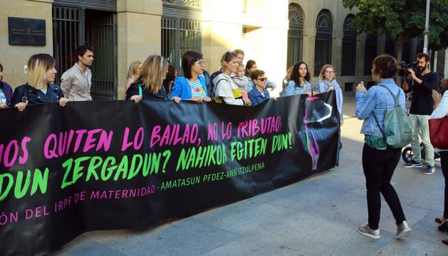 Foto de los representantes de las madres afectadas con una pancarta en la puerta del Palacio de Navarra, minutos antes de la reunión.