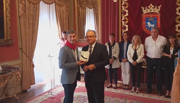 Alberto Undiano Mallenco recibe el cuarto 'Pañuelo de Pamplona' de manos del alcalde de Pamplona, Enrique Maya.