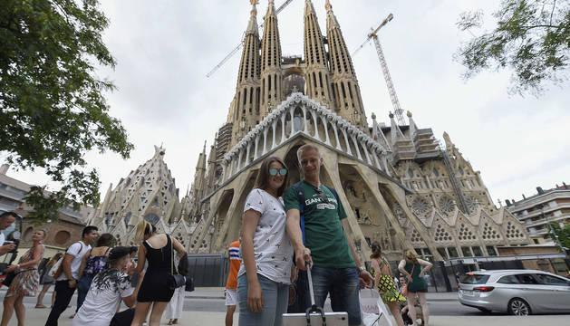 Varios turistas se fotografían frente a la Sagrada Familia en Barcelona.
