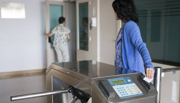 Una trabajadora registra su entrada a la empresa mediante un sistema de tarjeta de acceso.