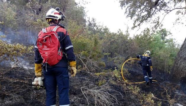 Imagen de dos bomberos trabajando en la zona afectada por el incendio en Oricain.