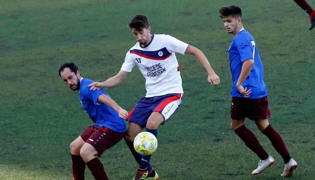Eder Abaurrea, de la Mutilvera, controla la pelota entre David Sádabay Aarón Martín, de la Peña.