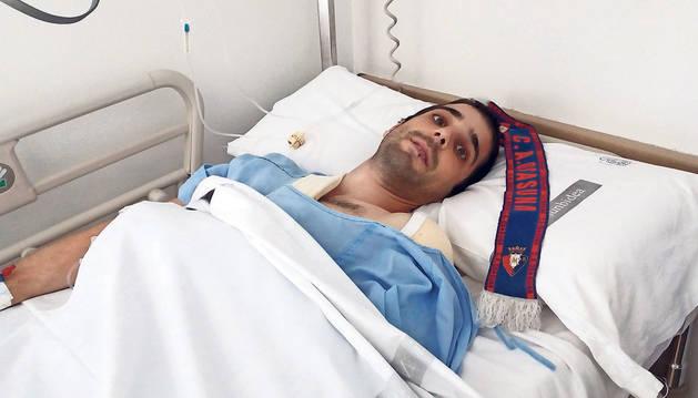foto de Oihan Górriz Muruzábal, de 26 años, en la habitación del Complejo Hospitalario donde se recupera de las heridas. Junto a él, la bufanda rojilla que tanto ánimo le da