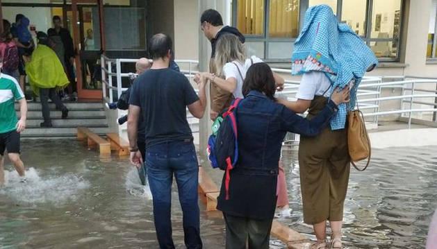 Bancos del gimnasio y brazos de padres y profesores para entrar ayer al colegio San Pedro de Mutilva. El patio, totalmente anegado.