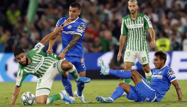 Nabil Fekir es objeto de falta por los jugadores del Getafe Mauro Arambarri y Damián Suárez. Su compañero bético Canales sigue la jugada.