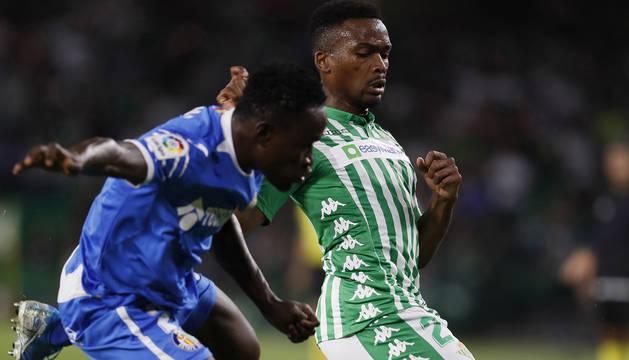 El centrocampista camerunés del Real Betis Kaptoum (d) protege un balón ante Djené, del Getafe.