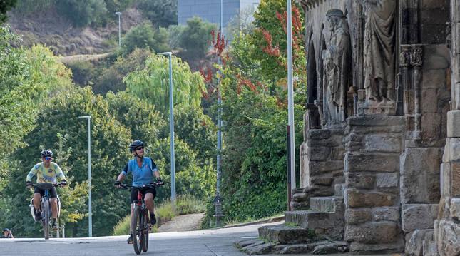 Dos personas acceden en bicicleta al entorno de Curtidores y contemplan la iglesia del Santo Sepulcro.
