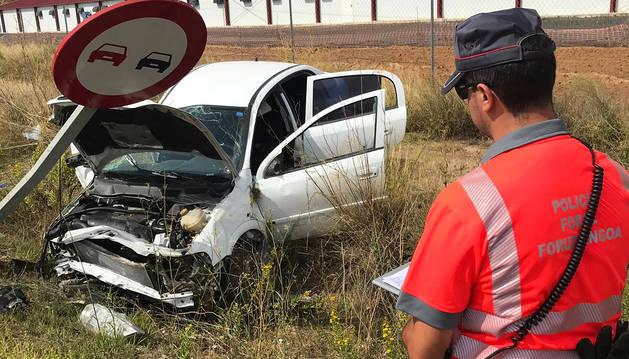 Un agente observa el estado en el que quedó el automóvil tras el accidente de tráfico.