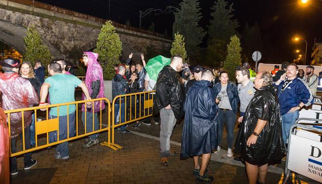 El público que iba a asistir al festival Music Planet-'Un viaje a los 90'S' en Tudela se cubre de la lluvia.