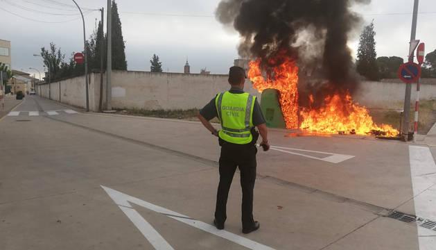 Un agente de la Guardia Civil ante las llamas que consumen uno de los contenedores.