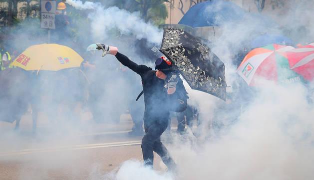 Un protestante antigubernamental arroja un bote de gas a los policía.