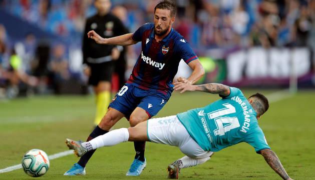 El defensa del Levante, Jorge Miramón, intenta superar la entrada del centrocampista de Osasuna, Rubén García.