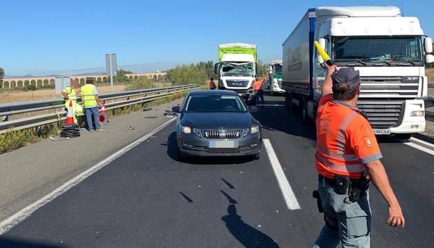 Un agente de la Policía Foral regula el tráfico en la AP-15, dirección a Tudela, durante las retenciones producidas por el accidente.